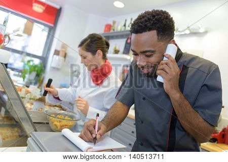 portrait of happy seller on call in butchery