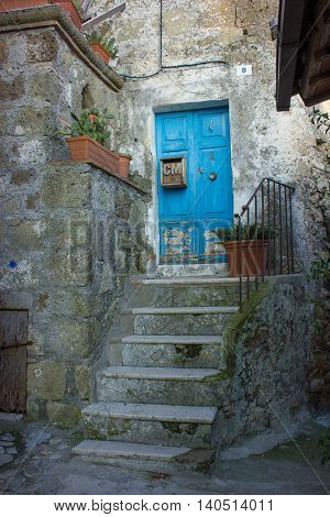 A bright blue woody door in a small Medieval town in Italy