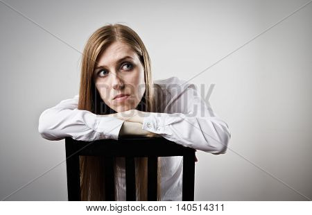 Sad and Unhappy woman in white is sitting.