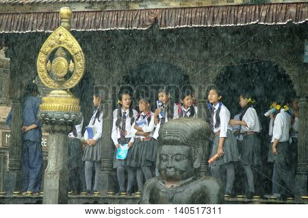KATHMANDU CIRCA AUGUST 2012 - Young students shelter from the monsoon rain in a temple circa August 2012 in Kathmandu.