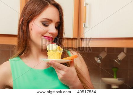 Woman eating delicious cake with sweet cream and fruits on top. Appetite and gluttony concept.