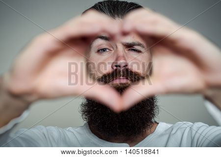 handsome young man with long beard and moustache on face holding hands in heart shape on grey background in studio