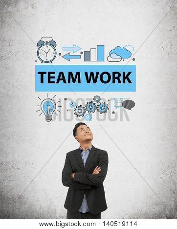 Businessman in dark suit is standing in front of concrete wall with team work sketch on it looking up and smiling. Concept of teambuilding in modern company