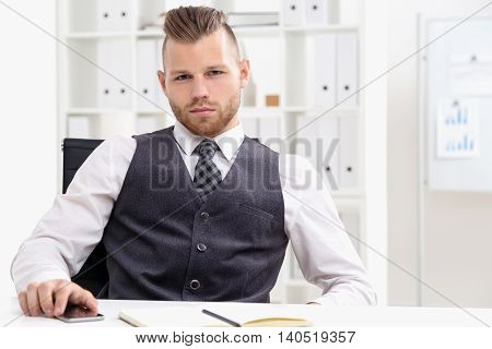 Serious businessman at work looking at camera and holding his cell phone. Concept of CEO representation