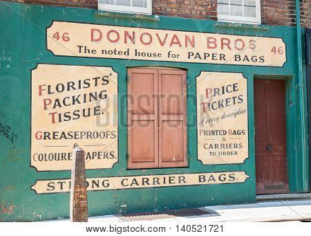 London, England - August 2, 2103; Faded original style signwritten wall Donovan Bros business marketing their products at 46 Gun Street Spitalfields London