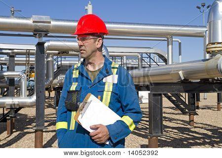 Male Gas Field Operator Inspects Compressor Site