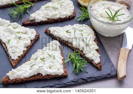 Pumpernickel bread with feta cream cheese rosemary lemon and garlic dip on slate board horizontal