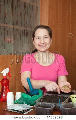 Mature Woman Sows Seedlings