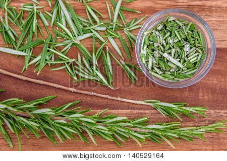 Sprigs of rosemary, and stripped and chopped rosemary (in a glass bowl) on a wood cutting board