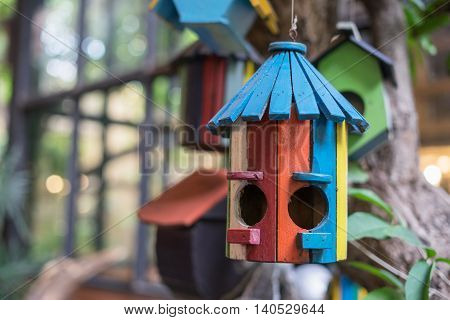 wooden birdhouse in red orange yellow pink green blue and white hang on tree surrounded green tree plant in the garden or park outdoor