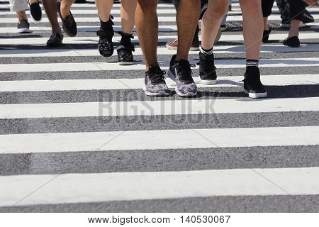 close-up on unidentified people legs crossing street