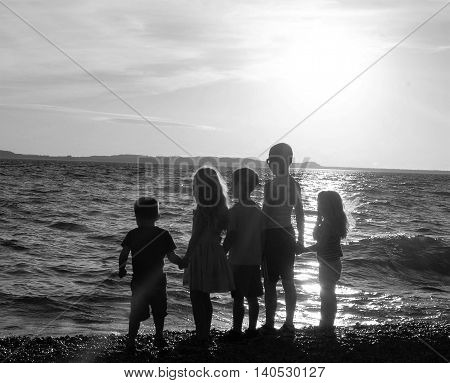group of children looking out over water lake ocean sunset holding hands family siblings