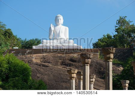 MIHINTALE, SRI LANKA - MARCH 12, 2015: Sculpture of a seated Buddha in front. Religious landmark  of the city Mihintale, Sri Lanka