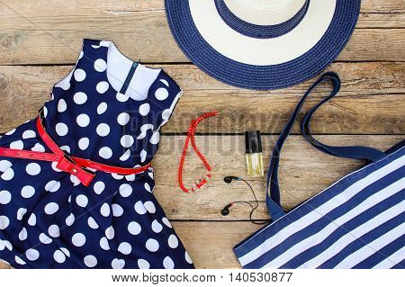 Summer clothing and accessories: dress, purse, hat, headphones, perfume, handbag and beads on old wooden background.