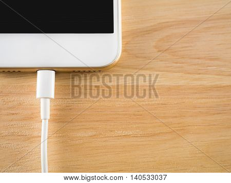 Top view (Flat Lay) of smart phone charging with USB cable on wooden texture background Copy space Horizontal