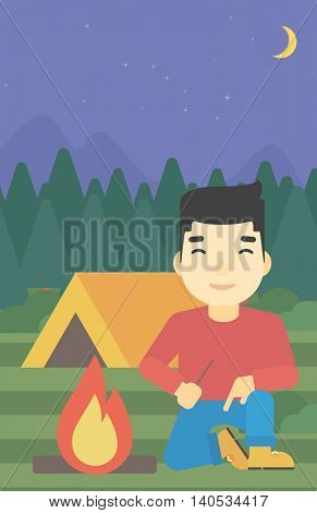 An asian man kindling a campfire on the background of camping site with tent. Tourist relaxing near campfire. Vector flat design illustration. Vertical layout.
