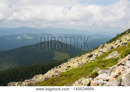 Mountain landscape. Amazing wild nature view of deep evergreen forest landscape on sunlight at middle of summer. Natural green scenery of cloud stones with moss on mountain slopes that look as valley on background. Ukraine Gorgany.