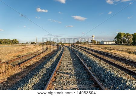 Two curved railroad tracks and one straight. One of the curved tracks has not been used for a long time judging by the rust on it.