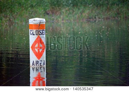 Floating Closed Area to Boating Warning Sign in Lake Water