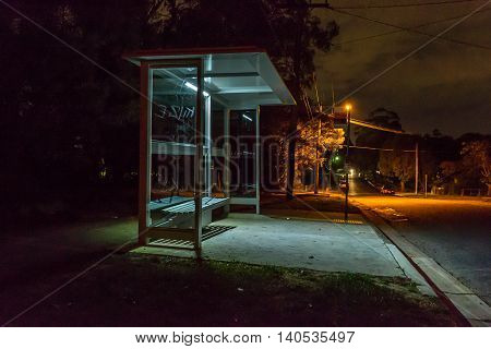 Empty bus shelter at night. Cars are parked down the road. graffiti is scratched into the glass.