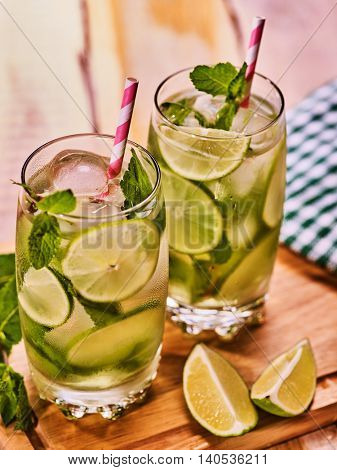 Alcohol drink. On wooden boards two glasses with alcohol drink and ice cubes. A drink number three hundred cocktail mohito with knife and mint leaf. Country life. Light background. Top view.