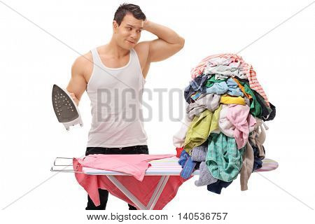 Confused young man looking at a pile of clothes for ironing and scratching his head isolated on white background
