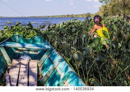 Puerto Pollo, Paraguay on August 8, 2015: An indigenous girl sitting next to a small fishermen's boat in Puerto Pollo at Rio Paraguay in Paraguay's Pantanal