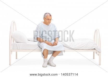 Worried mature patient sitting on a hospital bed and looking at the floor isolated on white background