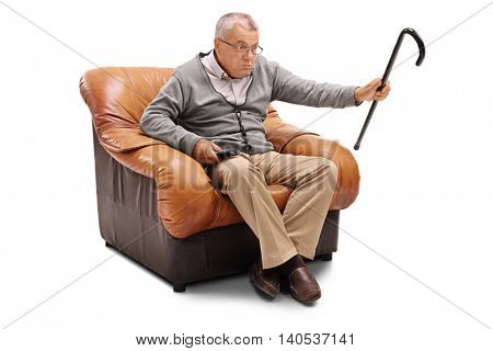Annoyed senior man watching TV seated on an armchair isolated on white background