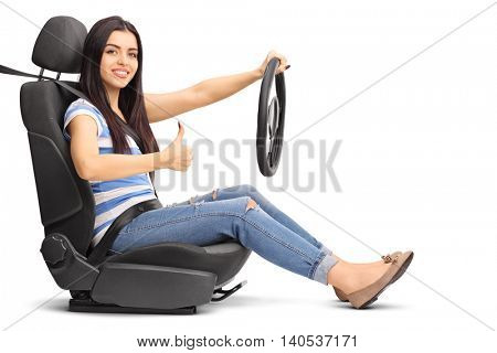 Young female driver sitting on a car seat and giving a thumb up isolated on white background