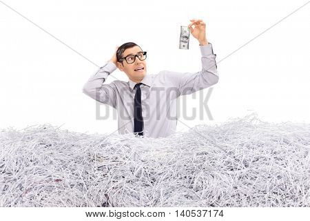 Worried businessman holding a dollar in a pile of shredded paper isolated on white background
