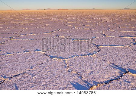 Salar de Uyuni: The sunrise at the salt lake creates a beautiful pattern. In the distance a jeep is driving over the salt lake