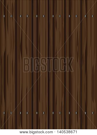 A fence made of softwood planks showing the wood grain and darkened with age