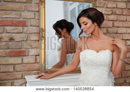 Beautiful young bride standing front of mirror, turning away head, looking down.