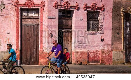Camaguey, Cuba on January 3, 2016: Cuban men riding bicycles through a street in the historic Caribbean city center of Camaguey