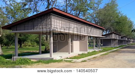 row of six, tan, partially open storage and parking shelters beside a golf course, under pine trees, Songkhla, Thailand