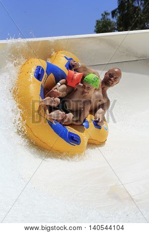 Rhodes Greece-July 7 2016:Father and son drive with tube on the rafting slide in the Water park.Rafting slide is one of many popular game for adults and children in park.Water Park is located on the island of Rhodes in Greece and one of the must largest