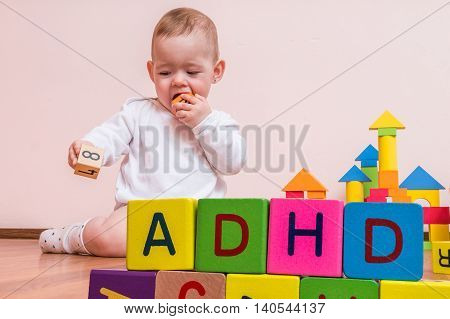 ADHD concept. Baby is playing with colorful cubes with letters.