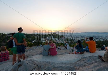 ATHENS-AUGUST 22: Tourists enjoy sunset on Areopagus hill on August 22 2014 in Athens Greece. Areopagus hill is located just bellow the entrance of the Acropolis.