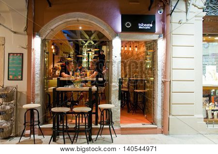 CORFU-AUGUST 25: Young men have drinks in a local restaurants on August 25 2014 on Corfu island Greece. Kerkyra is a city on the island of Corfu in the Ionian Sea in Greece.