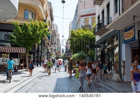 ATHENS-AUGUST 22: People shop on Ermou Street on August 22 2014 in Athens Greece. Ermou street is a main shopping street in Athens. Greece.