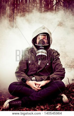 Boy In Gas Mask With Crossed Legs In Front Of Fog