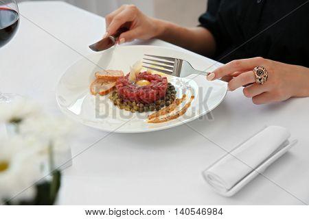 Woman eating beef tartare in restaurant