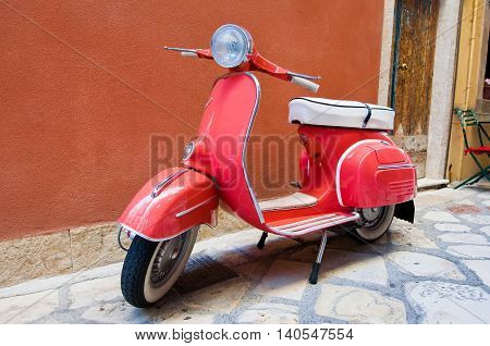 CORFU-AUGUST 22: Vespa scooter parked on Kerkyra street on August 22 2014 on Corfu island. Greece. Vespa is an Italian brand of scooter manufactured by Piaggio.