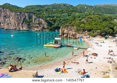 CORFU-AUGUST 26: Palaiokastritsa beach people sunbathe on the beach on August 262014 on the island of Corfu Greece. Palaiokastritsa is a village with famous beaches in the North West of Corfu.