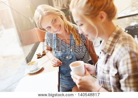 Sideways Portrait In White Colours Of Two Female Friends In Café. Fresh And Beautiful Shot Of Girl I