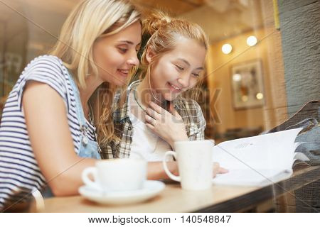 Two Young Blond Girls Reading Fashion Magazine In Comfy Coffee Shop Near The Window. Nice Woman With