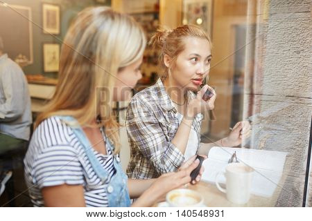 Two Young Women Sitting In A Café With Coffee Near The Window. Blond Girl In Checked Shirt And Bun O