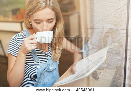 Pretty Young Woman Sipping Coffee And Reading Magazine Near The Window. Nice And Warm Shot Of Caucas