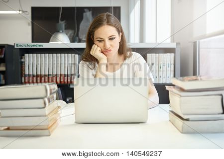 Attractive Young Student With Confused Face Expression Sitting At The Table In The University Librar